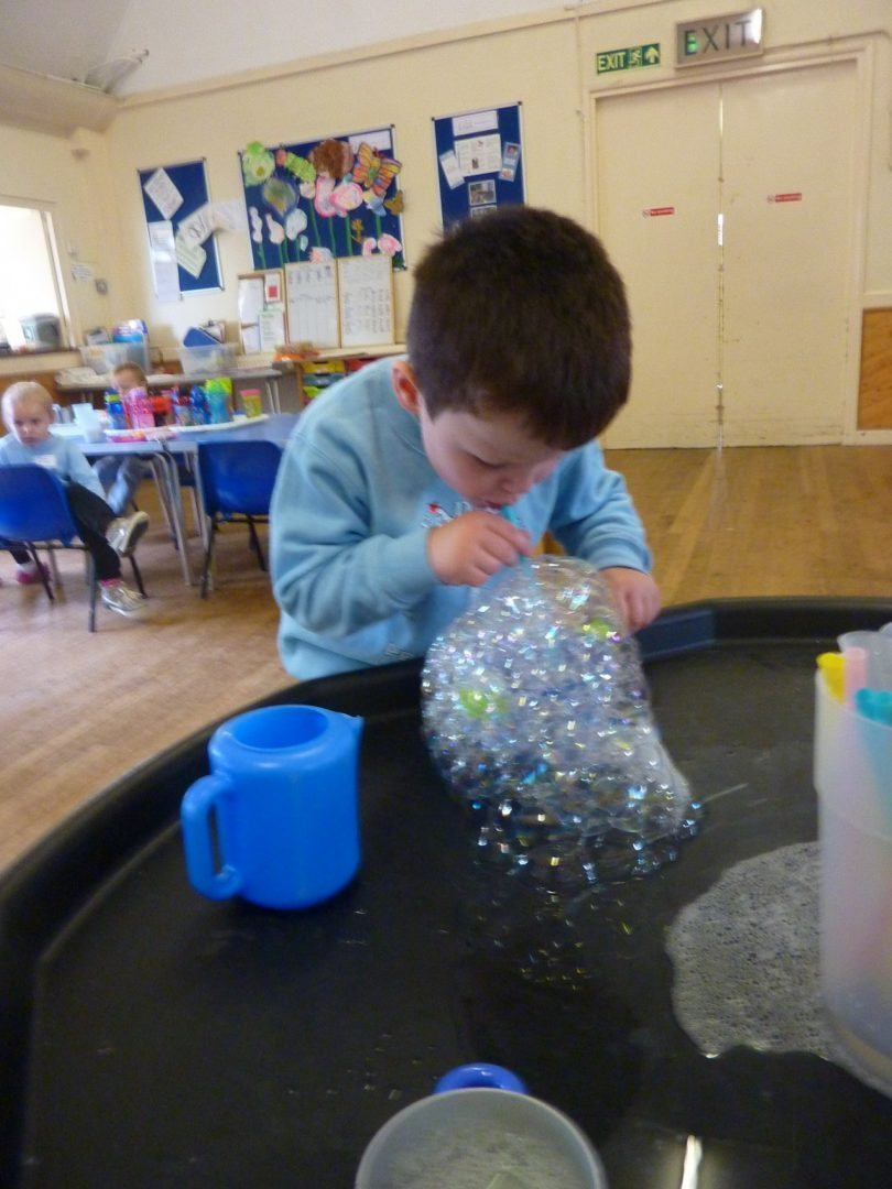 Blowing bubbles for sensory play and oral motor strength.